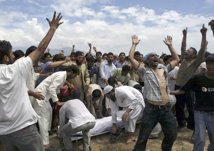 FILE - In this Aug. 14, 2008, file photo, Kashmiri Muslims shout slogans demanding independence from India as others prepare to carry the body of a man who was shot during a protest during his funeral in Srinagar, India. India's leaders are anxiously watching the Taliban takeover in Afghanistan, fearing that it will benefit their bitter rival Pakistan and feed a long-simmering insurgency in the disputed region of Kashmir, where militants already have a foothold. (AP Photo/Dar Yasin, File)