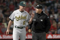 Oakland Athletics manager Bob Melvin, left, questions umpire Mark Carlson on a video replay decision during the seventh inning of the team's baseball game against the Los Angeles Angels in Anaheim, Calif., Saturday, Sept. 18, 2021. (AP Photo/Alex Gallardo)