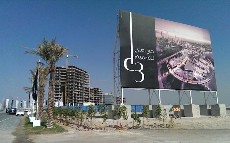 In this Jan. 30, 2014 photo, with a billboard showing the Dubai Design District, construction work is being carried at the project site in Dubai, United Arab Emirates. Dubai and luxury are nearly synonymous. The city is home to the world's tallest tower, massive manmade islands in the shape of palm trees and a fleet of police cars that include a Ferrari, Lamborghini and a $2.5 million Bugatti Veyron. To boost its glamour factor and economy, the city has its eyes set on the multi-billion dollar a year global fashion industry, which is currently dominated by the U.S., Europe and Japan. (AP Photo/Aya Batrawy)