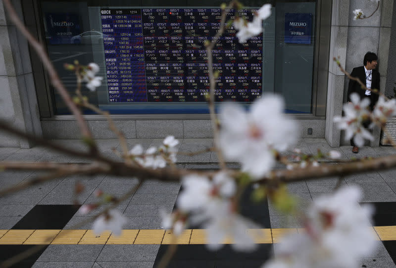 FILE PHOTO - A man stands next to an electronic stock quotation board as cherry blossoms are in full bloom outside a brokerage in Tokyo March 25, 2013. REUTERS/Issei Kato