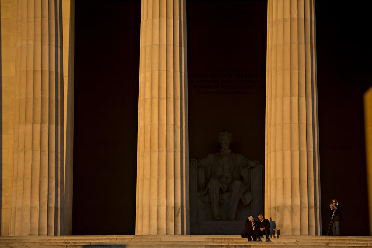 <p>Visitors sit at the Lincoln Memorial at sunrise in Washington on Saturday, Jan. 20, 2018. The U.S. government officially entered a partial shutdown early Saturday. (Photo: Andrew Harrer/Bloomberg via Getty Images) </p>