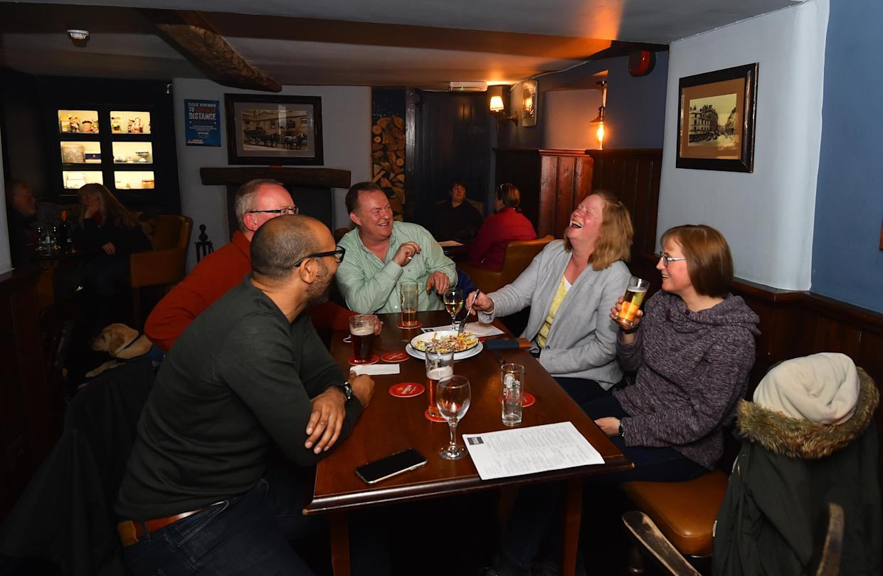 People socialize at the Old Sun Inn pub on May 17, 2021, in Buxton, England. (Nathan Stirk/Getty Images)