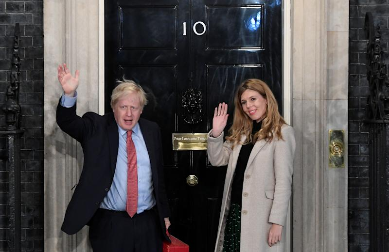 Britain's Prime Minister Boris Johnson and his partner Carrie Symonds gesture as they arrive at 10 Downing Street on the morning after the general election in London, Britain, December 13, 2019. REUTERS/Toby Melville