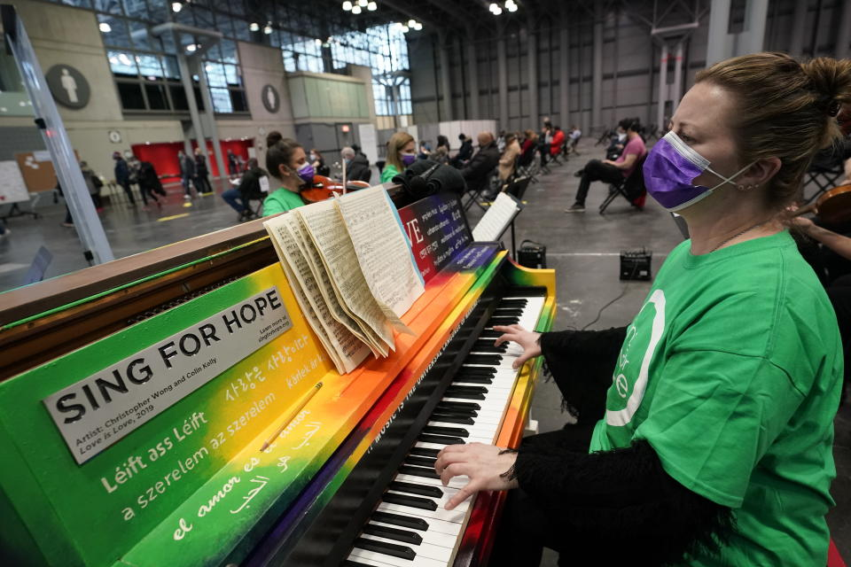 Pianist and CUNY music professor Barbara Podgurski plays with a string quartet for people who had received a COVID-19 vaccination and were waiting during the observation period, at the Jacob K. Javits Convention Center, Thursday, March 18, 2021, in New York. The convention center, which early in the pandemic served as a temporary field hospital, has been converted into a massive vaccination site. (AP Photo/Kathy Willens)