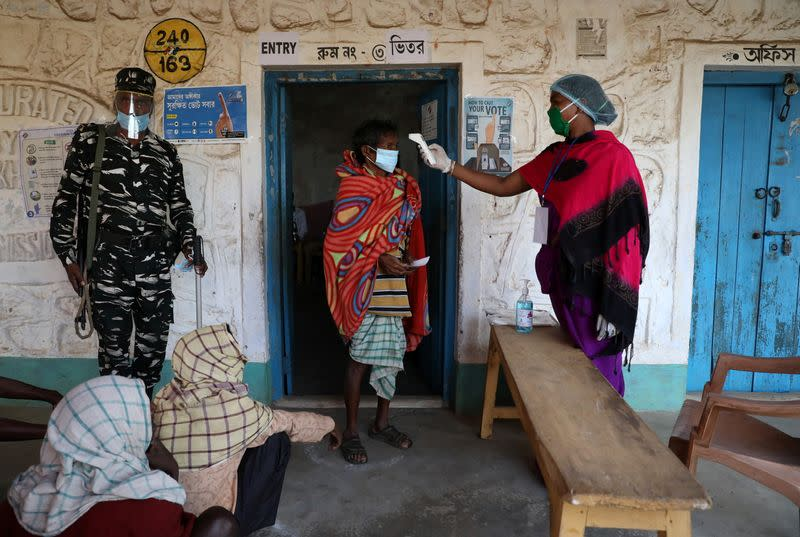A woman checks the temperature of a voter before he casts his vote at a polling booth in Purulia