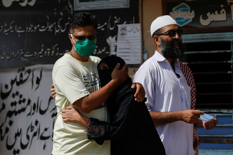 Family members mourn the death of a relative who was killed in a plane crash, outside a morgue in Karachi