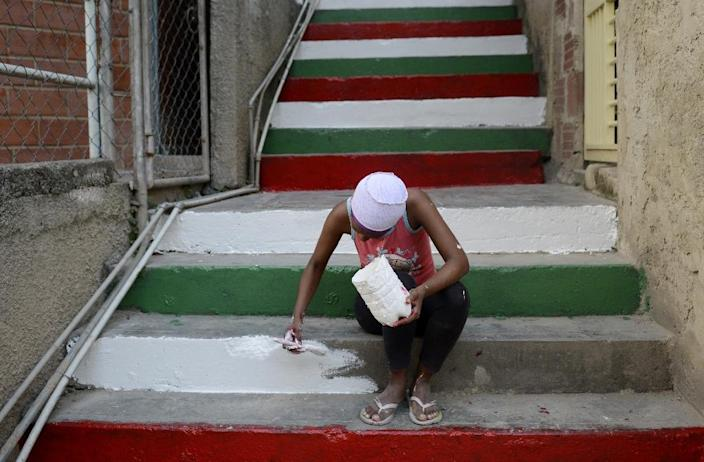 A woman paints stairs with Christmas colors at the Jose Felix Ribas community in low-income Petare neighbourhood in Caracas on December 4, 2013 (AFP Photo/Leo Ramirez)