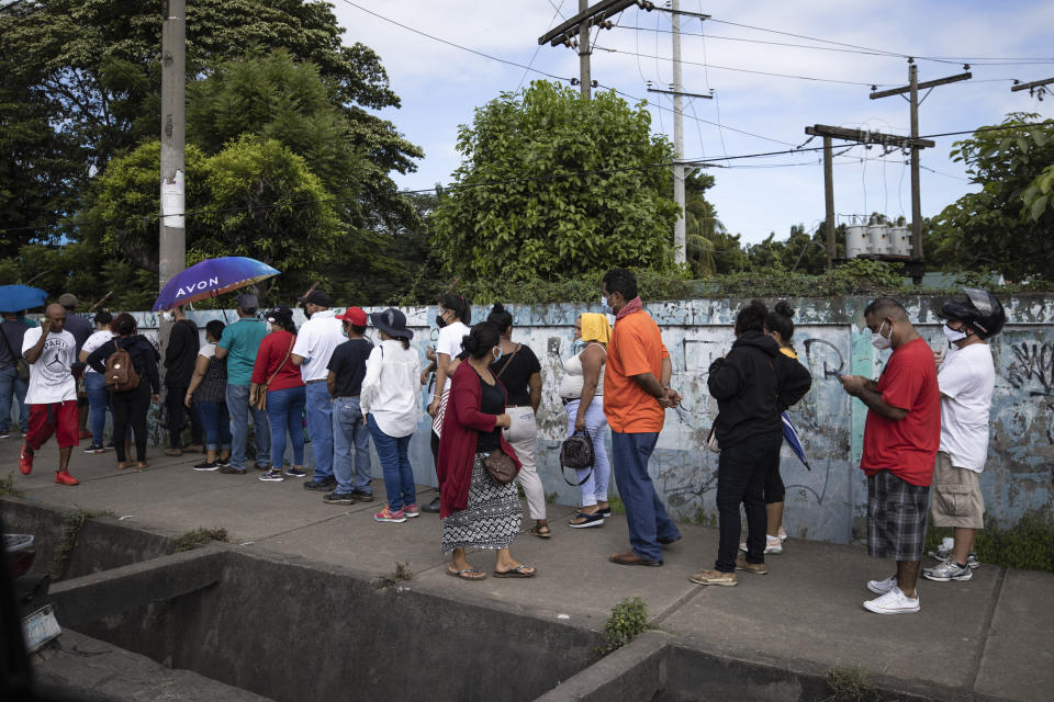 People wait in line to be vaccinated with the AstraZeneca COVID-19 vaccine, in Managua, Nicaragua, Monday, Sept. 20, 2021. (AP Photo/Miguel Andres)
