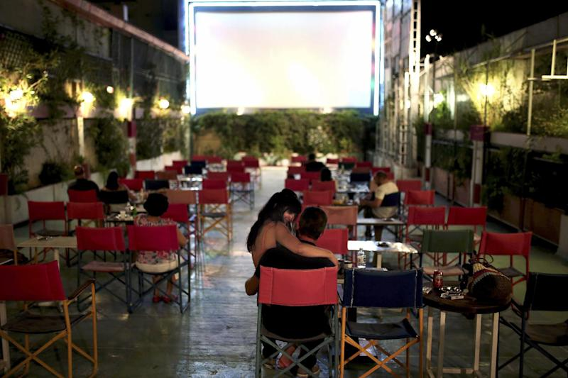 Cinema-goers watch a film at the Palas, one of Athens' oldest open-air theatres in the middle-class district of Pangrati, on July 30, 2014