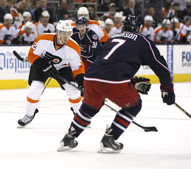 Philadelphia Flyers' Michael Raffl (12) prepares to shoot past Columbus Blue Jackets' Jack Johnson (7) during the first period of an NHL hockey game on Saturday, Dec. 21, 2013, in Columbus, Ohio. (AP Photo/Mike Munden)