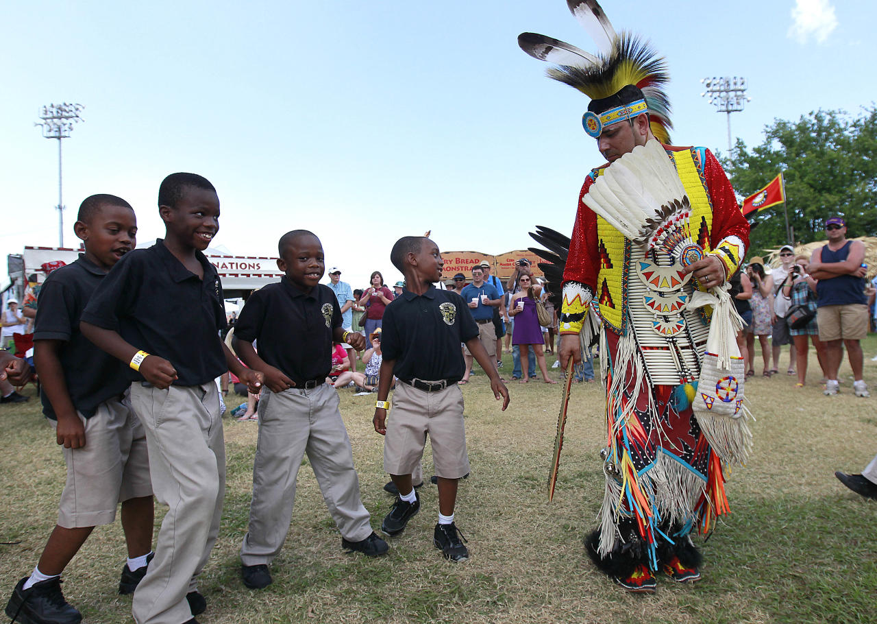 Children from the John Dilbert Charter School of New Orleans volunteer to dance with a member of the Ojibway tribe during a pow wow performance by Native Nations Intertribal at the Native American Village at the New Orleans Jazz and Heritage Festival in New Orleans, Friday, May 4, 2012. (AP Photo/Gerald Herbert)