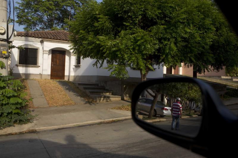 In this Wednesday, May 7, 2014 photo, a security guard is reflected in a car mirror in front of the house where U.S. citizen William James Vahey lived, near the American Nicaraguan School in Managua, Nicaragua where he worked as teacher from 2013-2014. Vahey, 64, killed himself on March 21, 2014 - two days after agents in Houston filed for a warrant to search a computer thumb drive that belonged to him. The storage device contained pornographic images of at least 90 boys, ages 12 to 14, who appeared to be drugged and unconscious, according to the FBI. (AP Photo/Esteban Felix)