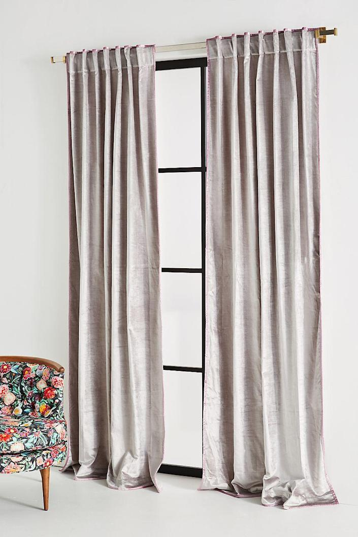 "Anthropologie is known for its unique whimsical designs, and this cascading velvet curtain set is no exception. Available in a rich yet muted blue, bright peach, or warm gray (and in four sizes), these window treatments will get the job done, no matter what you want them to do. Plus, the subtle piping along the edges adds much-welcomed charm. It may be simple, but drapery in one solid color still can offer a playful feel—even if the color palette is more muted. $78, Anthropologie. <a href=""https://www.anthropologie.com/shop/petra-velvet-curtain5?color=006&type=STANDARD&quantity=1"" rel=""nofollow noopener"" target=""_blank"" data-ylk=""slk:Get it now!"" class=""link rapid-noclick-resp"">Get it now!</a>"