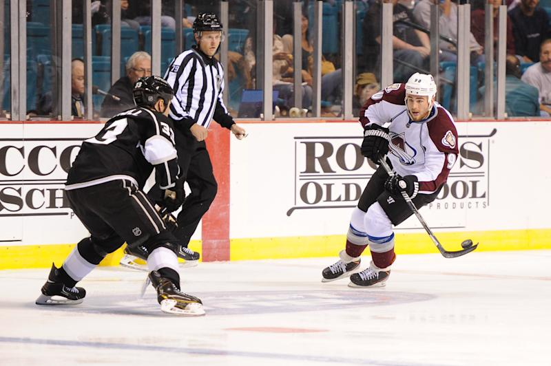 Colorado Avalanche center Ryan O'Reilly (90) controls the puck in front of Los Angeles Kings defenseman Willie Mitchell (33) in the first period of an NHL preseason hockey game on Saturday, Sept. 28, 2013, in Las Vegas. (AP Photo/David A. Cleveland Jr.)