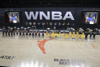 Members of the Phoenix Mercury, left, and Los Angeles Sparks stand for a moment of silence in honor of Breonna Taylor before a WNBA basketball game, Saturday, July 25, 2020, in Ellenton, Fla. (AP Photo/Phelan M. Ebenhack)