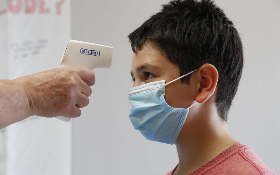 Amid concerns of the spread of COVID-19, sixth-grader Salih Tas wears a mask as he has his temperature checked by a teacher during a STEM summer camp in Wylie, Texas. (AP Photo/LM Otero)