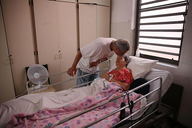 <p>Rafael Robles-Ortiz kisses his mother Josefina Ortiz who is staying at the Hermanitas de los Ancianos Desamparados facility which cares for the elderly as they deal with the aftermath of Hurricane Maria on Sept. 26, 2017 in San Juan, Puerto Rico. Mr. Robles-Ortiz is concerned for his mother and hopes aid — including fuel for the facilities generators, as well as food and medicine for his mother — gets through after Hurricane Maria, a category 4 hurricane, devastated the island. (Photo: Joe Raedle/Getty Images) </p>