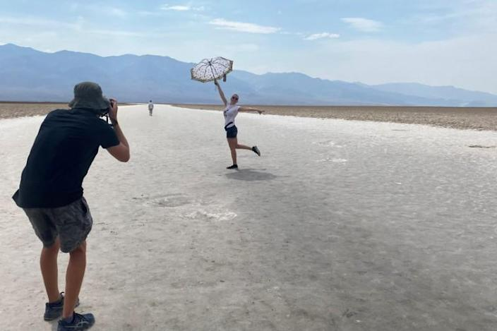 Tourist poses with an umbrella at Badwater Basin in Death Valley