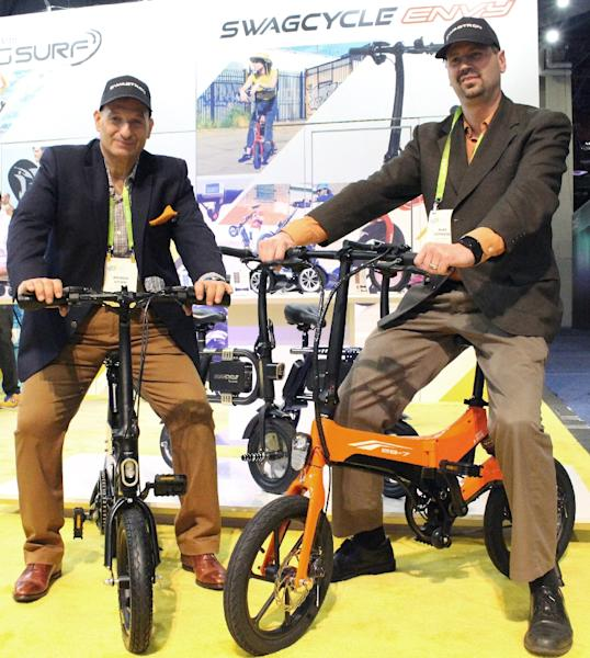 Andrew Koven (L) and Mike Johnson (R) of Swagtron pose on two of the US company's electric bicycle models at the 2018 Consumer Electronics Show in Las Vegas (AFP Photo/Glenn CHAPMAN)