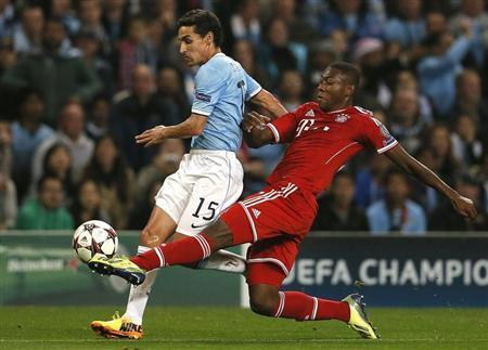 Manchester City's Jesus Navas (L) challenged by Bayern Munich's David Alaba during their Champions League soccer match at the Etihad Stadium in Manchester, northern England October 2, 2013. REUTERS/Phil Noble