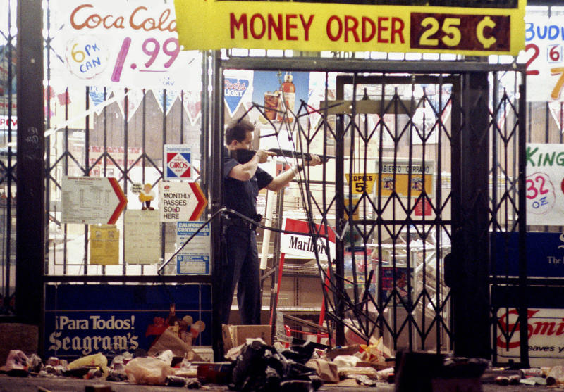 FILE - In this April 30, 1992 file photo, a Los Angeles police officer takes aim at someone attempting to steal something from a market in Los Angeles during the second night of rioting in the city in response to the acquittal of four police officers in the videotaped beating of Rodney King.  (AP Photo/John Gaps III, File)