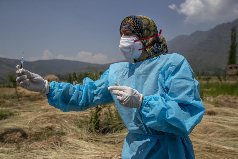A health worker prepares to administer a dose of the AstraZeneca vaccine for COVID-19 to a farmer in a paddy field in Tral village south of Srinagar, Indian controlled Kashmir, Saturday, June 5, 2021. (AP Photo/ Dar Yasin)