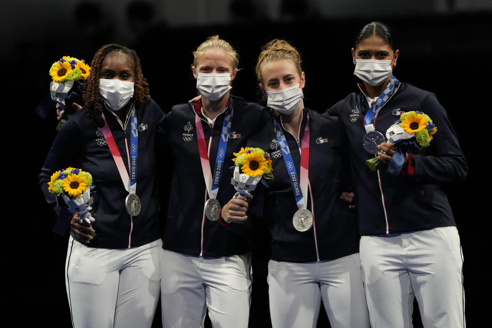 Silver medalists of France celebrate on the podium of the women's Foil team final at the 2020 Summer Olympics, Thursday, July 29, 2021, in Chiba, Japan. (AP Photo/Hassan Ammar)