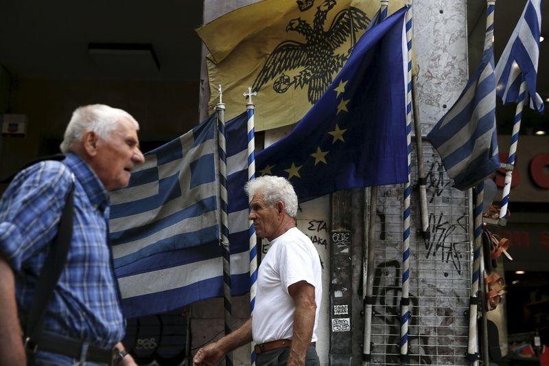 People make their way next to Greek national flags and a European Union flag in Athens