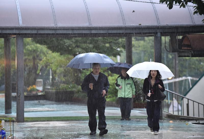 Rain lashed most of Japan on election day as Typhoon Lam approaches the country (AFP Photo/Kazuhiro NOGI)