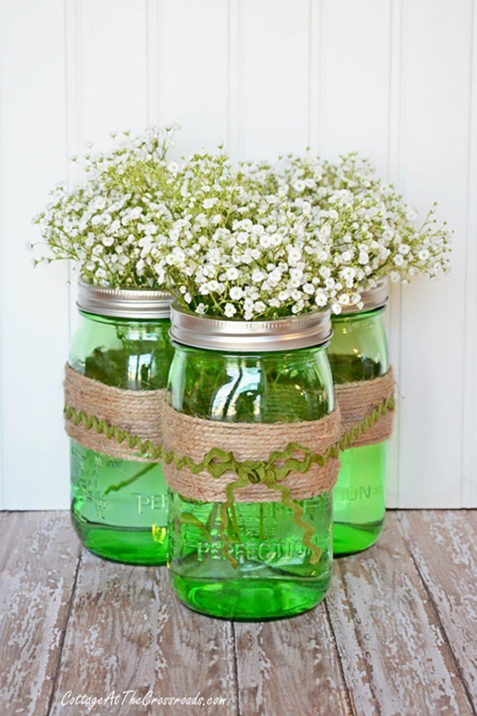 """<p>The hue makes them festive enough for St. Patrick's Day, but these jars are so pretty you'll want to leave them out all spring!</p><p><strong>Get the tutorial at <a href=""""http://cottageatthecrossroads.com/easy-spring-centerpiece-with-green-ball-jars/"""" rel=""""nofollow noopener"""" target=""""_blank"""" data-ylk=""""slk:Cottage at the Crossroads"""" class=""""link rapid-noclick-resp"""">Cottage at the Crossroads</a>. </strong></p><p><a class=""""link rapid-noclick-resp"""" href=""""https://www.amazon.com/Ball-1440069110-Bands-Mouth-quart/dp/B00NZVTVAQ/ref=sr_1_4?tag=syn-yahoo-20&ascsubtag=%5Bartid%7C10050.g.4036%5Bsrc%7Cyahoo-us"""" rel=""""nofollow noopener"""" target=""""_blank"""" data-ylk=""""slk:SHOP GREEN MASON JARS"""">SHOP GREEN MASON JARS</a></p>"""