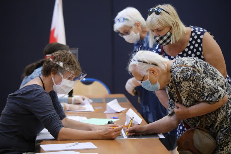 People attend a voting during the presidential election at a polling station in Warsaw