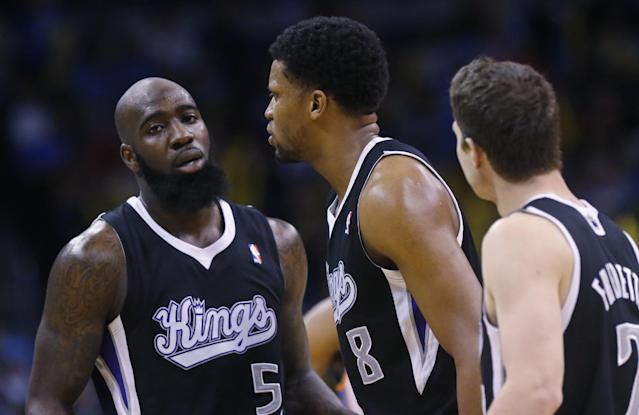 Sacramento Kings forward Rudy Gay (8) is surrounded by teammates forward Quincy Acy (5) and guard Jimmer Fredette (7) after being ejected from the game in the fourth quarter of an NBA basketball game against the Oklahoma City Thunder in Oklahoma City, Sunday, Jan. 19, 2014. Oklahoma City won 108-93. (AP Photo/Sue Ogrocki)