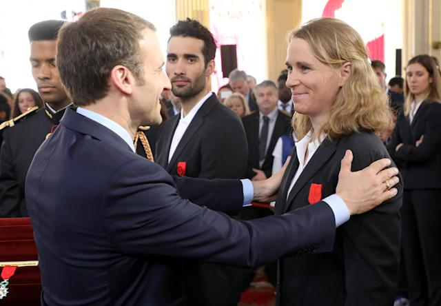 French biathlete Anais Bescond (R) is awarded Chevalier of the Legion of Honour (Legion d'honneur) by French President Emmanuel Macron (L), flanked by France's five-time Olympic champion Martin Fourcade (C), during an award ceremony gathering French athletes that competed in the 2018 Pyeongchang Olympics winter Games, at the Elysee Palace in Paris, France, Avril 13, 2018. Ludovic Marin/Pool via Reuters