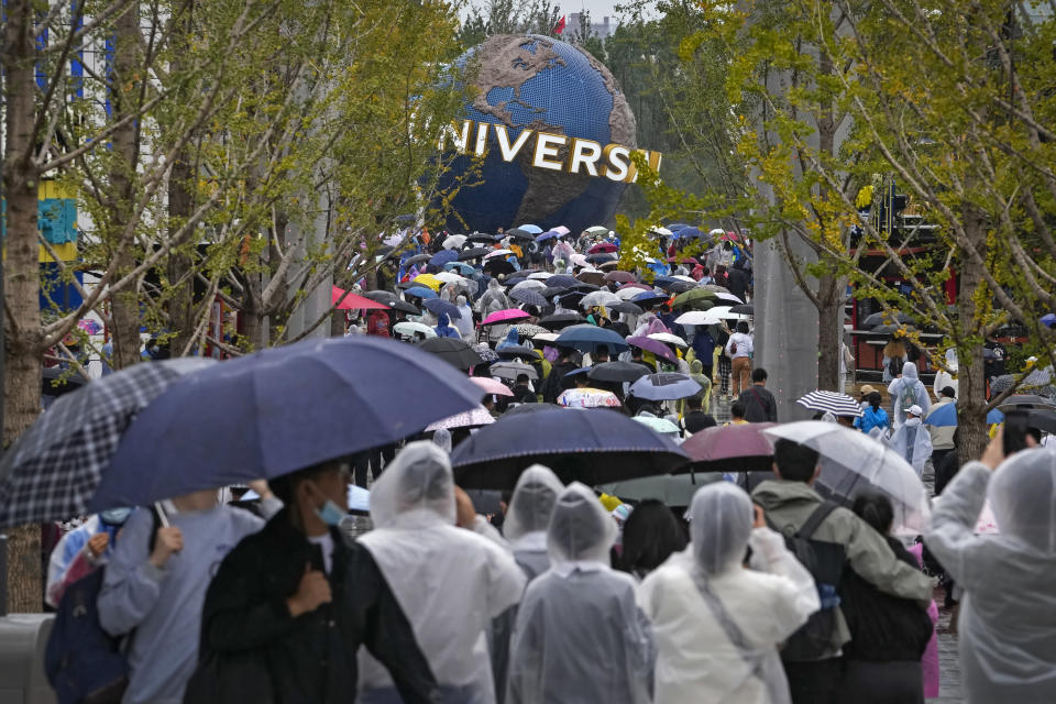 People wearing raincoats and carrying umbrellas walk through a plaza near the entrance of Universal Studios Beijing in Beijing, Monday, Sept. 20, 2021. Thousands of people brave the rain visit to the newest location of the global brand of theme parks which officially opens on Monday. (AP Photo/Andy Wong)