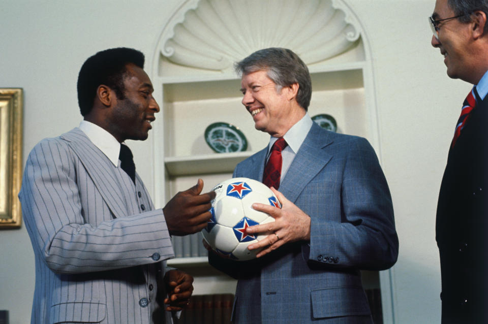 Brazilian soccer star Pele, who now plays with the New York Cosmos, gives a soccer ball to President Jimmy Carter during a White House visit.
