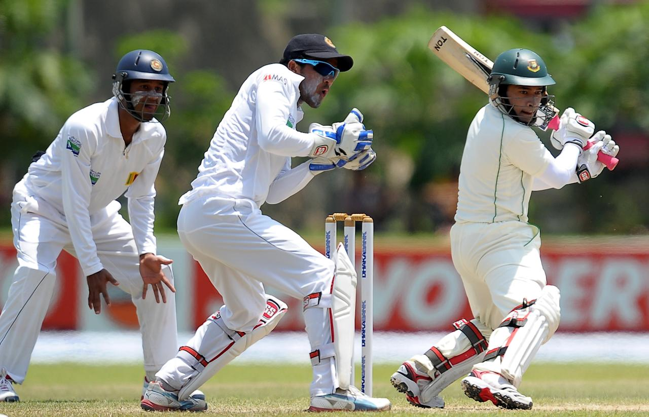 Bangladeshi captain Mushfiqur Rahim (R) is watched by Sri Lankan wicketkeeper Dinesh Chandimal (C) as he plays a shot during the third day of the opening Test match between Sri Lanka and Bangladesh at the Galle International Cricket Stadium in Galle on March 10, 2013.  AFP PHOTO/ LAKRUWAN WANNIARACHCHI        (Photo credit should read LAKRUWAN WANNIARACHCHI/AFP/Getty Images)