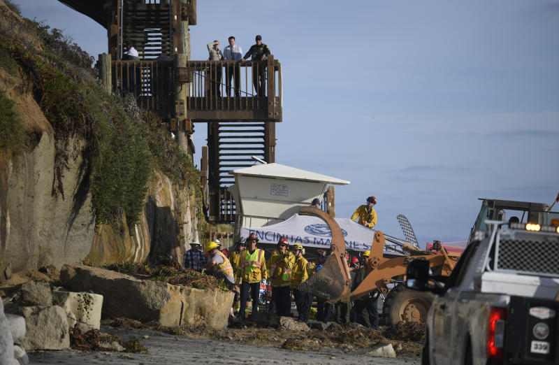FILE - In this Aug. 2, 2019 file photo search and rescue personnel work at the site of a cliff collapse at a popular beach in Encinitas, Calif. Three family members enjoying a day at a San Diego area beach were killed Friday when a huge slab of the cliff above plunged on to the sand. The collapse has raised questions about the stability of bluffs along California's 1,000-mile (1,600-kilometer) coast.(AP Photo/Denis Poroy,File)