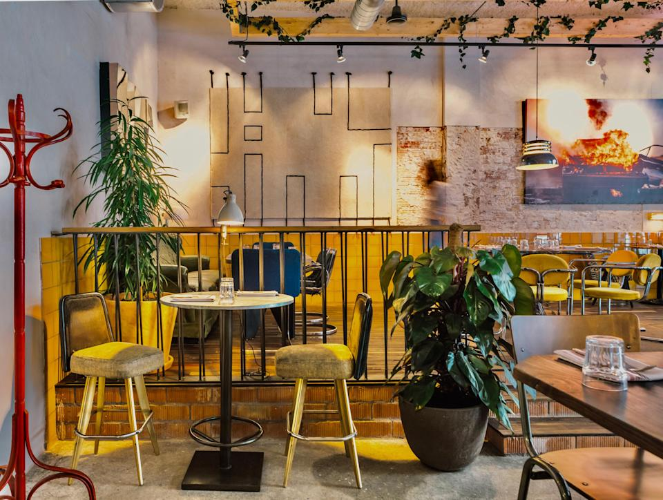 """<p><strong>Give us an overview.</strong> A huge photograph of a car in flames, tables where no two sets of seats is the same, metallic air-conditioning pipes that snake along the ceiling, a hot-red hat stand: Set in a former mechanic's garage, Benzina is clearly no ordinary Italian restaurant. There are also tunes—vinyl rock (The Stones, Creedence) that are hard not to sing along to, even with a mouth stuffed with pasta—plus cocktails served to start, to finish, or whenever you want them.</p> <p><strong>What is the crowd like?</strong> Some come just for the cocktails. The entrance and left side are packed with glammed-up stool-perchers lapping up social lubrication before they head onto more formal dinners. But the bulk of attendees are here to hunker down with comforting, unstuffy Italian food. If you burst into song, who cares? And if you burst out of your jeans—well, chef Nicola Valle has done his job.</p> <p><strong>What should we be drinking?</strong> A cocktail called Cocaine says it all: OK, it's named after the Eric Clapton song rather than the drug, but drinks are big business here: fun, potent, and naughty.</p> <p><strong>How's the food?</strong> Treat the appetizers like tapas: Mix juicy mouthfuls of buffalo mozzarella and tomatoes with rich gulps of eggplant alla parmigiana served with parmesan ice-cream. For mains, it's all about carb-loading: linguine with garlic, oil, and lobster; perfectly balanced risotto with salmon, celery and capers; even an old-school carbonara, all eggy and sticky. End with """"Sferamisu""""—a chocolate bomb filled with deconstructed tiramisú</p> <p><strong>Thoughts on the service?</strong> Owner Badr Bennis is as hands-on as any member of his team, doing some serving, tempting you with cocktails, and offering advice on what to order. He also has the all-important task of curating the soundtrack.</p> <p><strong>What's the bottom line?</strong> Come for one of those boozy, foodie, gossipy group nights out that you'll still be talking"""