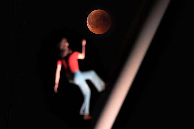 "<p>A ""blood moon"" eclipse is pictured with a sculpture by the American artist Jonathan Borofsky ""Woman walking to the sky"" on July 27, 2018 in Strasbourg, eastern France. (Photo: Frederick Florin/AFP/Getty Images) </p>"