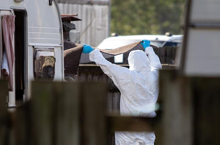Forensic teams inspect items near a caravan close to the scene in Berkshire on Saturday morning. (SWNS)