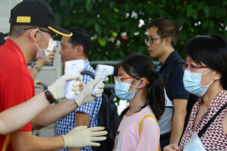 """People undergo temperature checks at the entrance during the """"Colours in Harmony"""" Chingay Parade at the F1 Pit Building on 31 January, 2020 in Singapore. (PHOTO: Getty Images)"""
