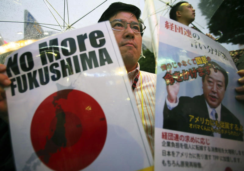 A participant holds a slogan and a photo of Japanese Prime Minister Yoshihiko Noda during a rally protesting the restart of Ohi nuclear power plant, in Tokyo, Sunday, July 1, 2012. Noda ordered the restarts of the plant's two reactors last month, saying people's living standards can't be maintained without nuclear energy. Protesters were against a return to nuclear power because of safety fears after the Fukushima accident and demanded the resignation of Noda. (AP Photo/Shizuo Kambayashi)