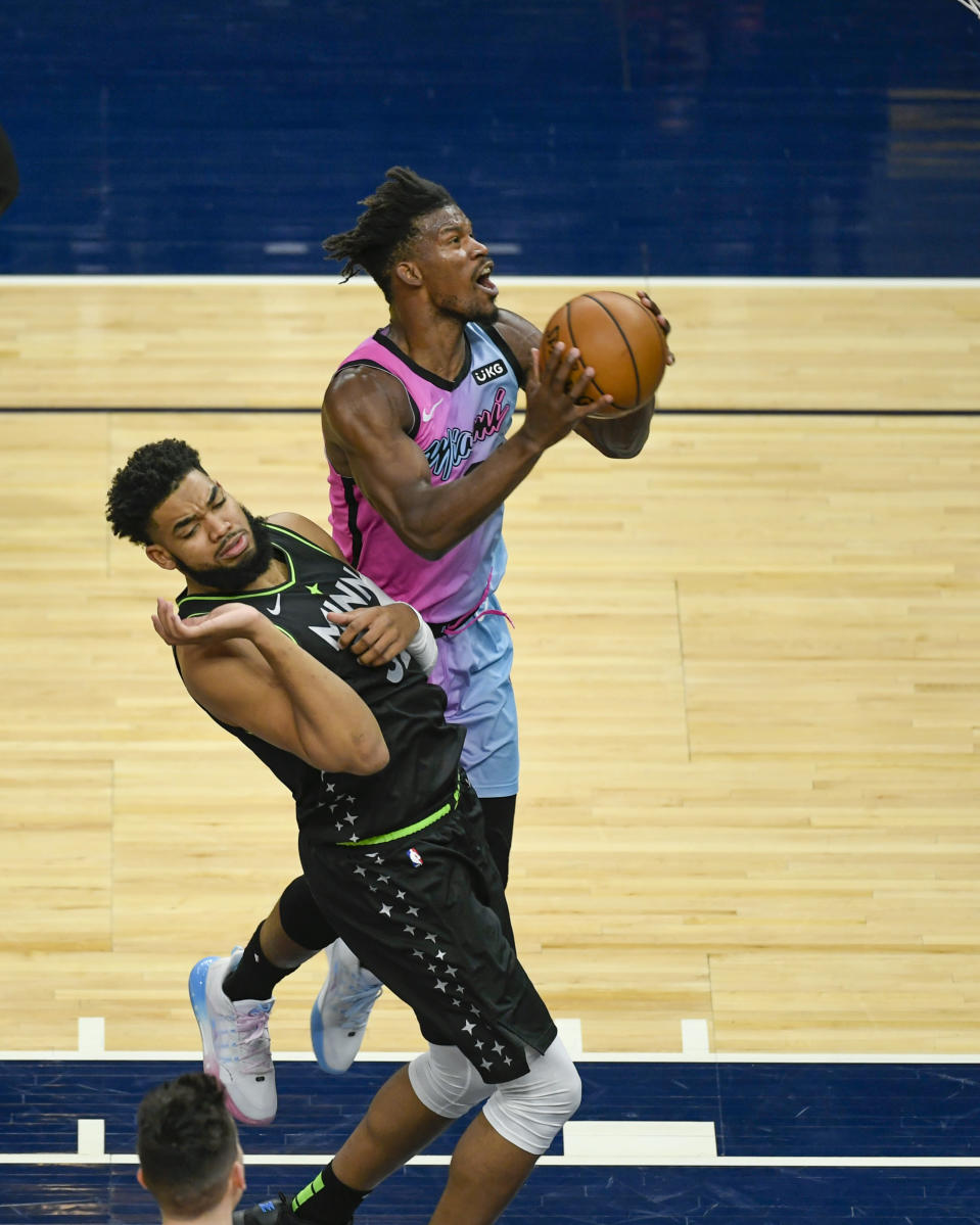 Minnesota Timberwolves center Karl-Anthony Towns, left, fouls Miami Heat forward Jimmy Butleras he goes up for a shot during the first half of an NBA basketball game Friday, April 16, 2021, in Minneapolis. (AP Photo/Craig Lassig)