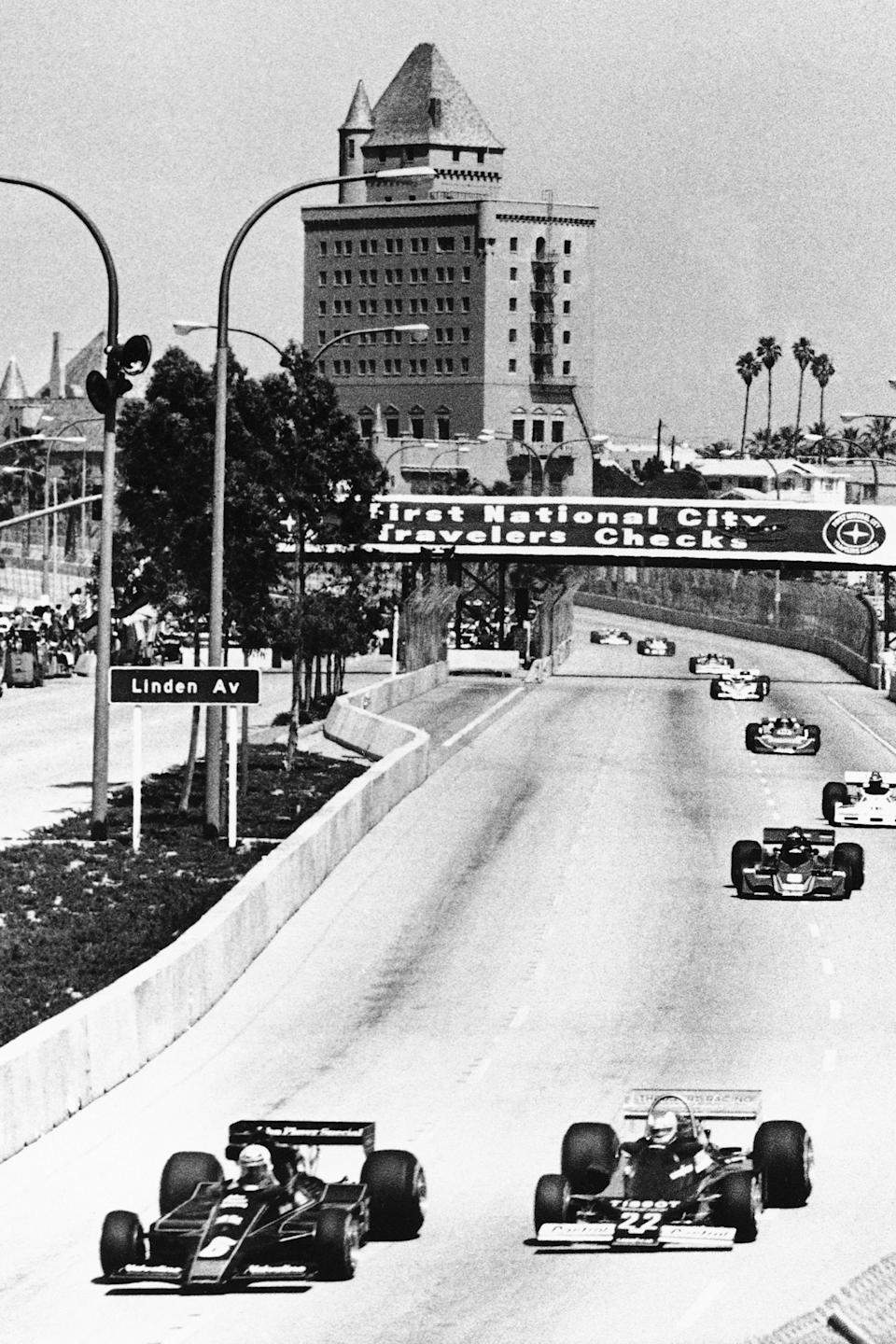 FILE - Formula One drivers Mario Andretti, left, and Clay Regazzoni of Switzerland lead the field through the streets of Long Beach, Calif., during the early laps of the Long Beach Grand Prix, in this April, 3, 1977, file photo. The Grand Prix of Long Beach opens 17 months after the pandemic ended the crown jewel's streak as one of the longest continuously-running street events in racing. The city closed its downtown streets for the first time in 1975 to host a street race that became one of the most prestigious events in both motorsports but also for successful, annual festivals (AP Photo/File)