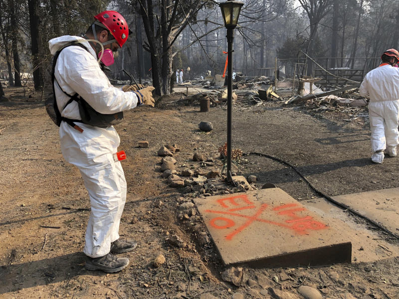 """When no remains are found, volunteers spray-paint a large, orange """"0'' near the house. (ASSOCIATED PRESS)"""