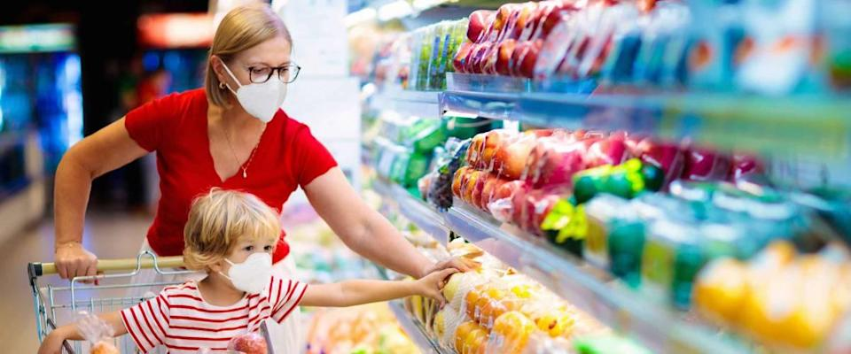 Mother and child wearing surgical face mask buying fruit in supermarket