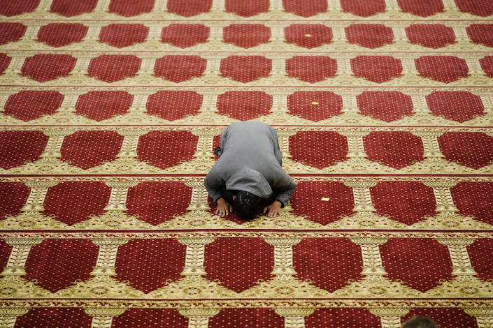 A worshipper prays upon arrival before he and and others gather to perform an Eid al-Fitr prayer at the Masjidullah Mosque in Philadelphia, Thursday, May 13, 2021. (AP Photo/Matt Rourke)