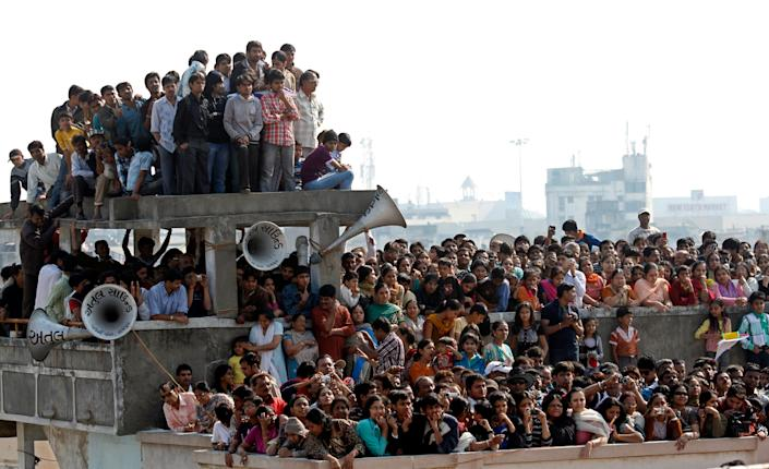 People stand on top of a house during a movie shootinRaipur, India.