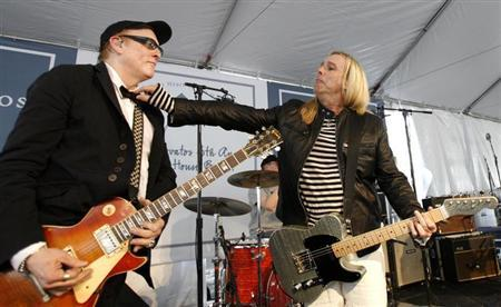 Robin Zander fixes the bowtie of Rick Nielsen as they perform with their band Cheap Trick at the 6th annual John Varvatos Stuart House Benefit in West Hollywood