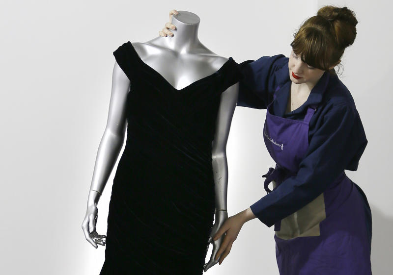 A Victor Edelstein midnight-blue velvet evening gown worn by Britain's Princess Diana when she danced with actor John Travolta in 1985 at the State dinner at the White House given by President and Mrs Reagan, is adjusted by house assistant Lucy Bishop at the Kerry Taylor auction rooms in London, Thursday, Feb. 28, 2013. The dress estimated to realise 200,000-300,000 pounds ( 310,000-464,000 US Dollars) will be sold in the Fit For a Princess auction in London on March 19. (AP Photo/Kirsty Wigglesworth)